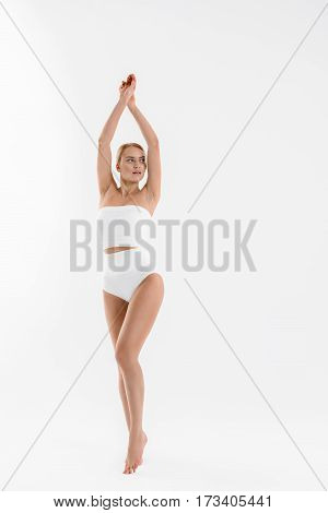 My figure is perfect. Sensual young woman is standing and raising arms up. Girl is wearing body-hugging underwear and has correction lines on face. Isolated
