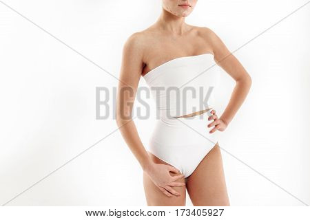 Plastic surgery will make my body perfect. Confident young woman is standing in tight underwear. Correction lines on her chin. Isolated and copy space in left side