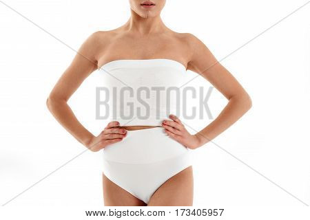 Fit young woman is standing with arms akimbo. Preparation for esthetic facial surgery. Isolated
