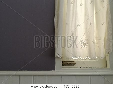 White Lace satin curtain hanging on window with sunlight semitransparent vintage light purple wall and white siding decoration interior room wall space