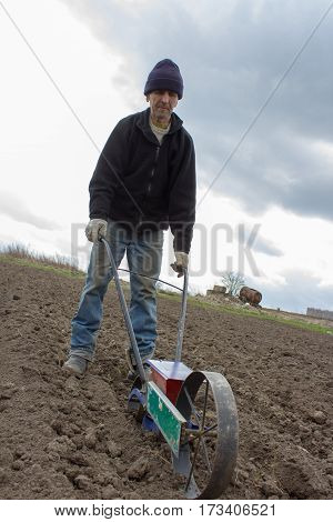 Grandpa spring sowing beet seed seeder field