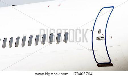Many porthole on the big white plane and the door