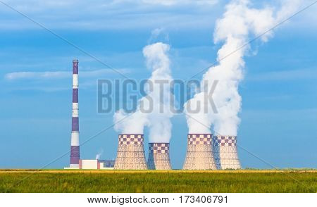 Thermal power plant рigh pipe with cooling towers on a green meadow