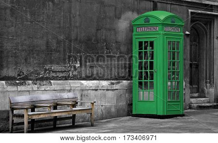 Green painted British phone booth and an old wooden bench in London, United Kingdom. Abstract concept