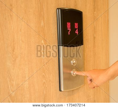 man is pressing lift button to other floor