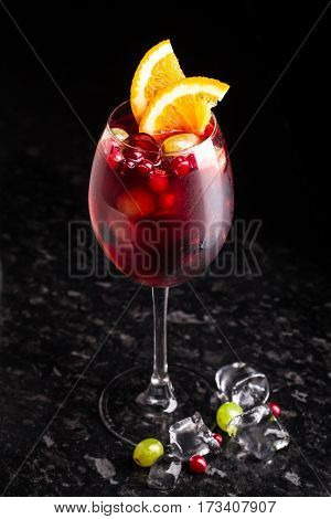 Delicious cocktail with cranberries and grapes on marble table
