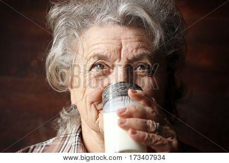 Grandmother drinks milk on a dark background
