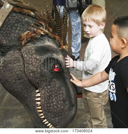 TUCSON, ARIZONA, FEBRUARY 20. The Tucson Expo Center on February 20, 2017, in Tucson, Arizona. Two Boys Pet a Young T-Rex, Tracey, at T-Rex Planet Tucson Expo Center, Tucson, Arizona