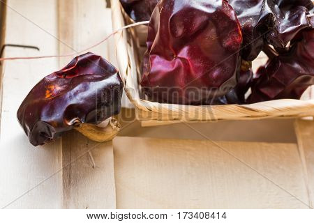 Spanish dried nyora peppers in wicker basket on wood box with thread for hanging close up dayligt