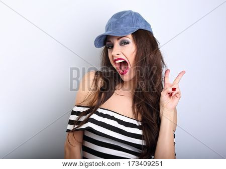 Crazy Young Female Model In Blue Hat Showing Rock Gesture With Wide Opened Mouth On Blue Background