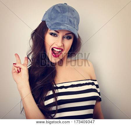 Crazy Young Female Model In Blue Hat Showing Rock Gesture With Opened Mouth On Blue Background With