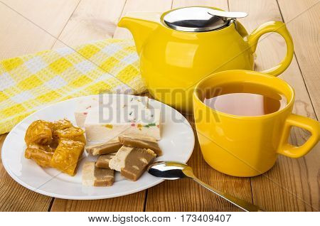 Oriental sweets in dish teapot and cup of tea on wooden table