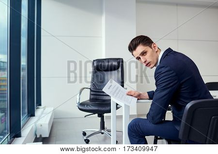 Businessman brunette in the hands of  contract documents  a modern office on background window.