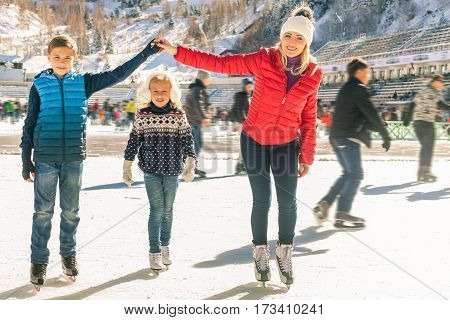 Happy family outdoor ice skating at rink. Mother and children has winter activities. Mom, kids. Medeo stadium. Almaty. poster