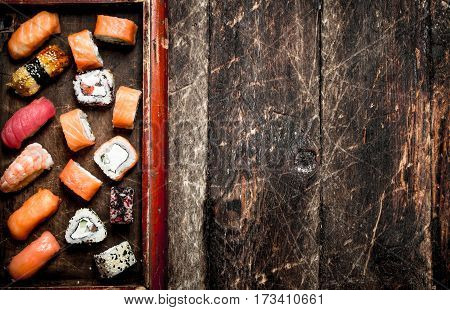 Japanese Food. Sushi And Rolls Seafood On The Old Tray. On The Old Wooden Background.