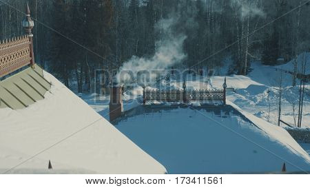 Roof of traditional snow-covered russian palace - terem in a forest.. Smoke coming from the chimney. Top view