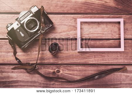 Old film camera with strap photo frame and film on wooden background. Vintage toned and top view.