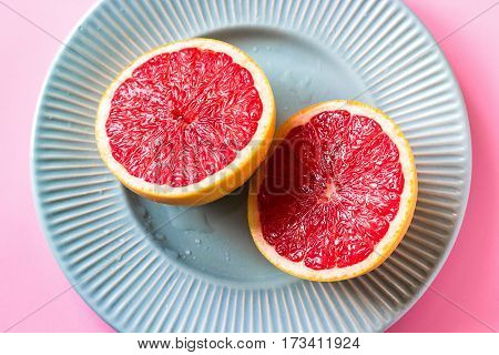 Beautiful appetizer fresh red grapefruit citrus fruit with half slice on blue plate and pink background close up top view natural vitamin C. Studio photography.