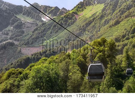 Cableway in the mountains from a moving cab on top of a mountain..