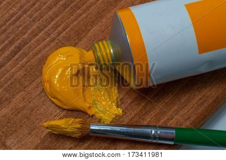 Yellow oil paint tube and the brush on the wooden background
