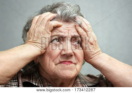 Grandmother stress and headache on a grey background