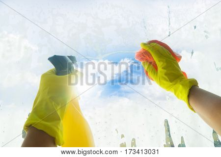 Spring cleaning - someones hands in yellow gloves cleaning window