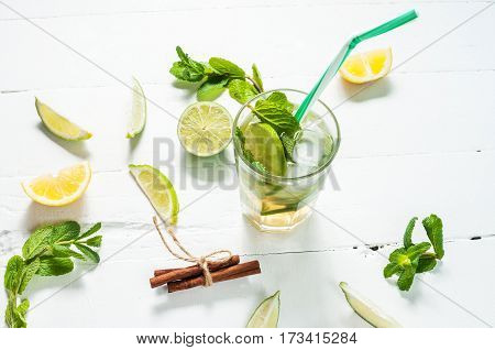 Mojito cocktail with lime and mint in highball glass on a wood white background.