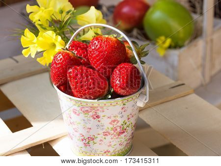 Fresh ripe strawberries in bucket on wood box in garden outdoors fruits in basket in background yellow flowers bright sunlight close up