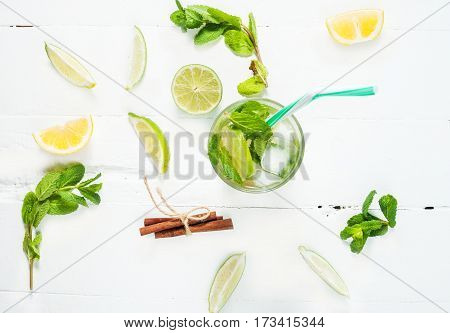 Mojito cocktail with lime and mint in highball glass on a wood white background. Top view
