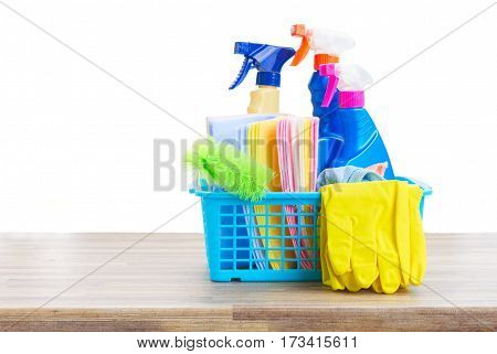 Spring cleaning concept - colorful spays and rubbers on wooden table border isolated on white background