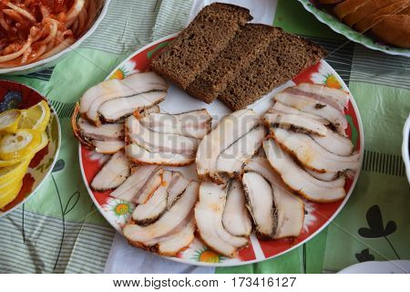 Food tray with delicious salami pieces of sliced ham sausage tomatoes salad.