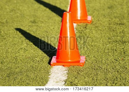 Orange cones on a white line on a green turf field