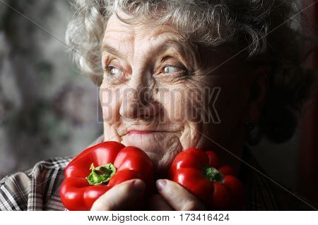 Grandmother with peppers on a dark background