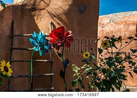A kiva ladder and a mixture of real and artificial flowers decorate an adobe wall in Old Town Albuquerque New Mexico.