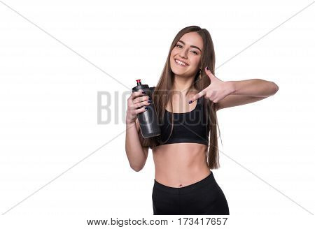 Portrait Of Smiling Young Sporty Woman With A Bottle Of Water Posing In Studio Isolated On White Bac