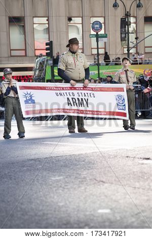 NEW YORK - 11 NOV 2016: Members from Boy Scouts of America hold banner for US Army personnel marching in Americas Parade up 5th Avenue on Veterans Day in Manhattan.