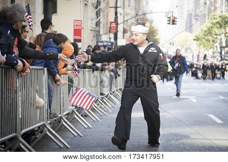 NEW YORK - 11 NOV 2016: US Navy, USN personnel from the USS Iwo Jima shakes hands with spectators during the Americas Parade up 5th Avenue on Veterans Day in Manhattan.