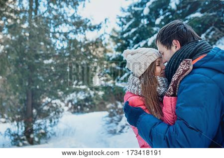 Man with a woman walking in the winter snow park