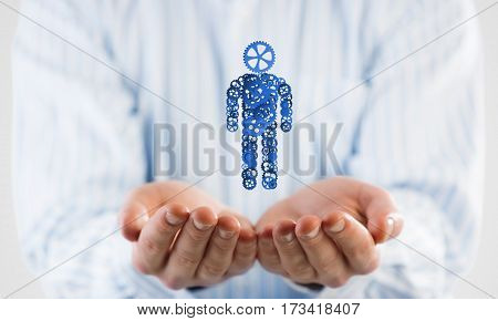 Close of male hands holding person gear figure in palm