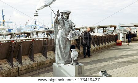 Hamburg, Germany - October, 10, 2016: Living statue street performer in Hamburg port poses to attract tourists and gapers. Living statues acting is a popular way to entertain passersby and tourists.