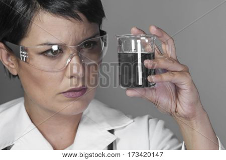 Test, Brunette woman in a laboratory, scientist studying a glass jar, wearing a white coat