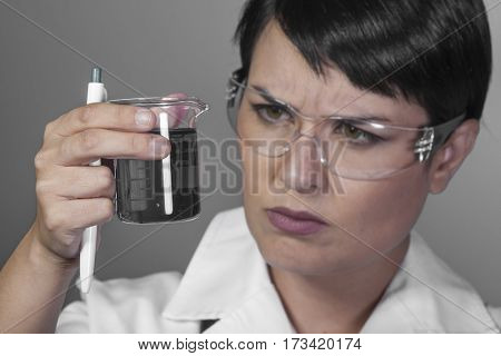 Dna, Brunette woman in a laboratory, scientist studying a glass jar, wearing a white coat