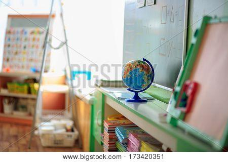 The Classroom In Kindergarten With School Desks And Chairs.