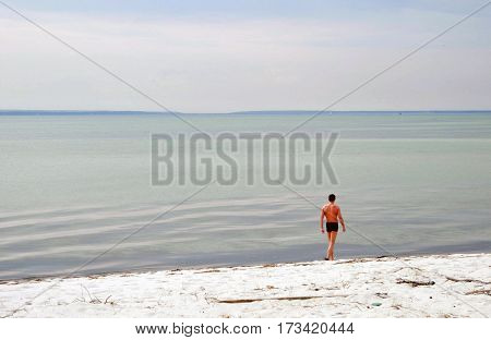 The man walks on the South Beach Hel spit in Poland.