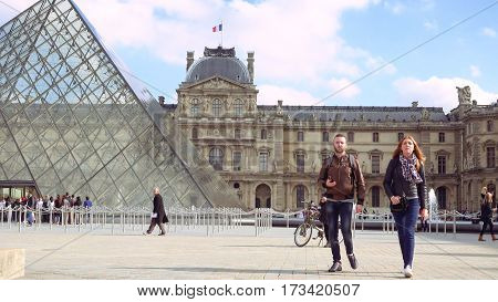 Paris, France - October, 14, 2016: tourists walking near glass pyramid in Louvre palace courtyard. Louvre and the Pyramid is one of most known landmarks in Paris.