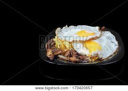 Fried eggs with potatoes and mushrooms on a black plate and a black background, with reflection.