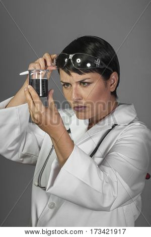 Researcher, Brunette woman in a laboratory, scientist studying a glass jar, wearing a white coat