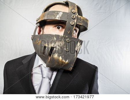 Angry businessman with iron mask on his face, is dressed in suit and tie