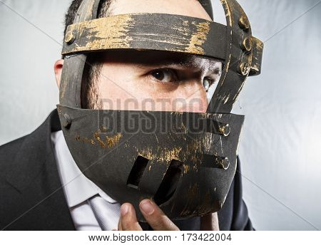 Crazy, Angry businessman with iron mask on his face, is dressed in suit and tie