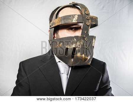 Furious, Angry businessman with iron mask on his face, is dressed in suit and tie